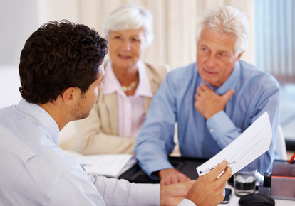 Discussing investment plans - Senior client with agent holding an agreement paper